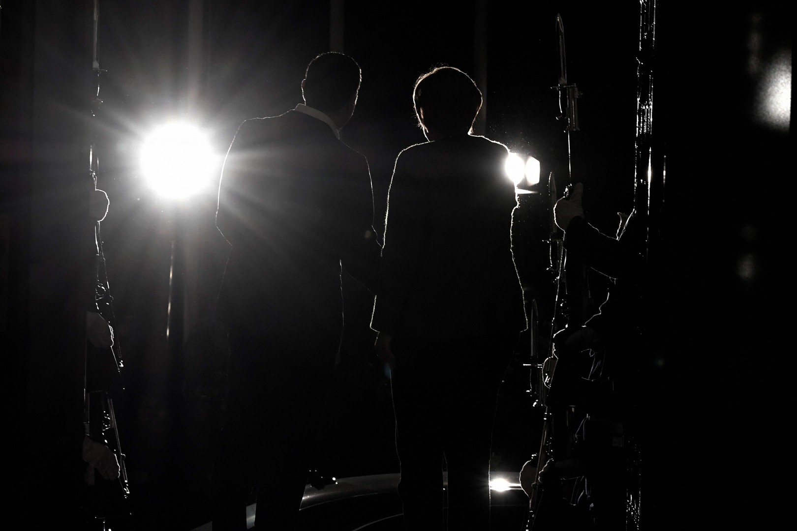 Greek Prime Minister Alexis Tsipras (R) and German Chancellor Angela Merkel are seen in silhouette while shaking hands upon Merkel's arrival in Athens on January 10, 2019. - German Chancellor Angela Merkel arrived in Greece amid tight security on January 10, 2019, as she looks to turn the page on the biting austerity measures that sparked major protests during her last official visit to Athens in 2014. (Photo by Louisa GOULIAMAKI / AFP)