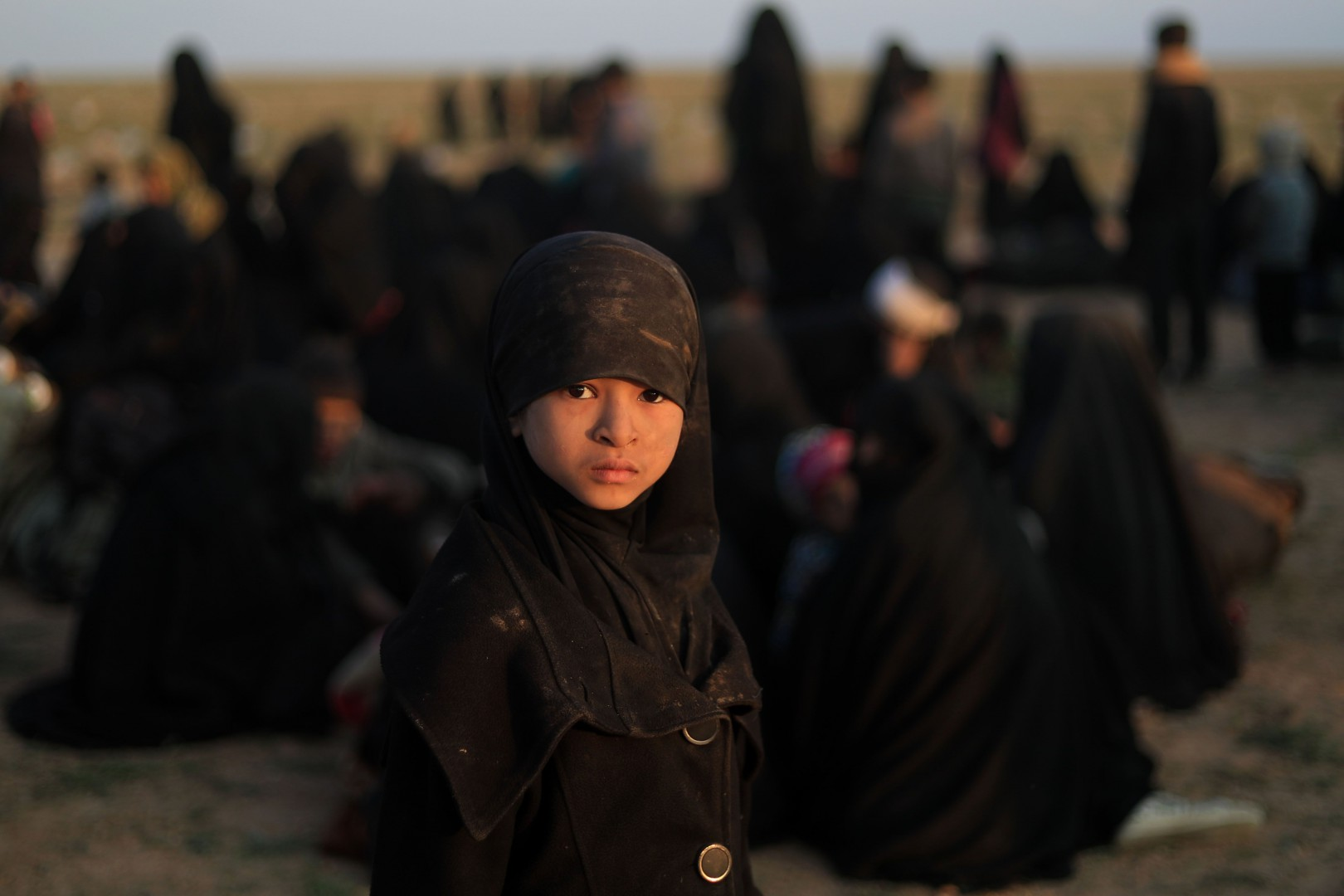 """TOPSHOT - A child who fled the Islamic State (IS) group's last embattled holdout of Baghouz  stands near families waiting to be searched by US-backed Syrian Democratic Forces (SDF) fighters (not pictured) in Syria's northern Deir Ezzor province, on February 22, 2019. - US-backed fighters trucked out civilians from the last speck of the Islamic State group's dying """"caliphate"""" in Syria on February 22, eager to press on with the battle to crush the jihadists. More than four years after IS overran large parts of Syria and neighbouring Iraq, and declared a """"caliphate"""", they have lost all of it but a tiny patch in the village of Baghouz near the Iraqi border. (Photo by Delil SOULEIMAN / AFP)"""