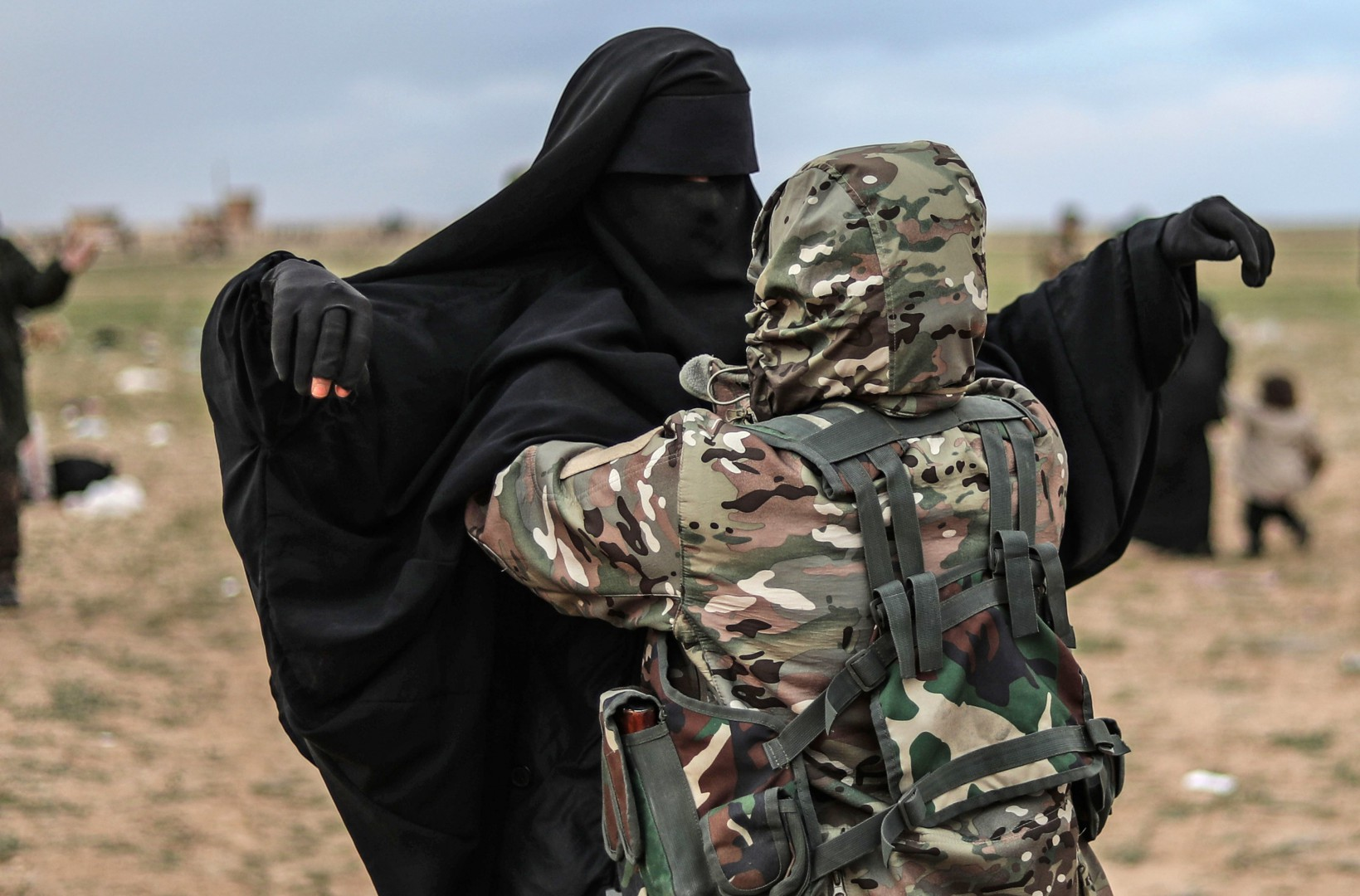 """Civilians evacuated from the Islamic State (IS) group's embattled holdout of Baghouz are searched by the US-backed Kurdish-led Syrian Democratic Forces (SDF) at a screening area, in the eastern Syrian province of Deir Ezzor, on February 27, 2019. - US-backed forces in eastern Syria screened and treated truckloads of suspected jihadists and relatives who left a village where the Islamic State group's """"caliphate"""" is making its last stand. The Kurdish-led SDF struggled to cope with the flow of people exiting the very last shred of a once-sprawling proto-state that claimed dominion over millions of people. (Photo by Delil SOULEIMAN / AFP)"""
