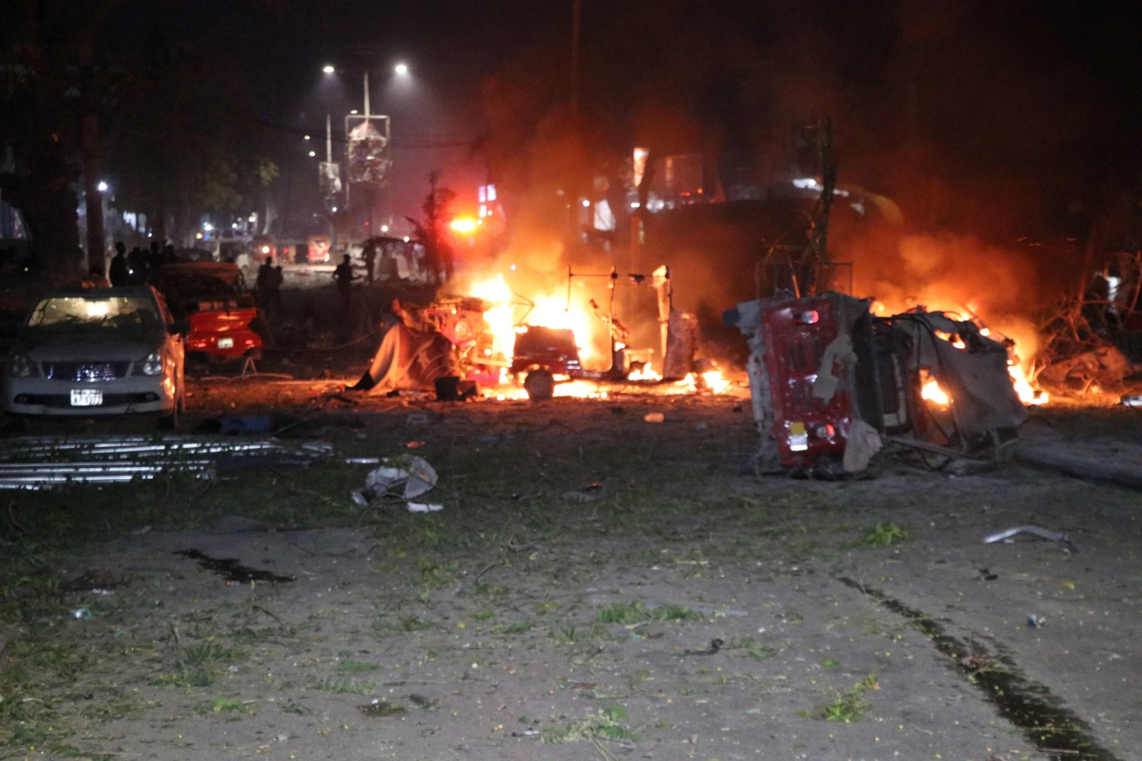 Shells of vehicles burn outside the Maka Al-Mukarama hotel in the Somalia capital, Mogadishu on February 28, 2019 after a car bomb exploded, killing at least five people and wounding 25 others. - Witnesses described how the blast ripped through one of the busiest streets of the capital in the early evening, filled with people relaxing after a day at work. (Photo by Abdirazak Hussein FARAH / AFP)