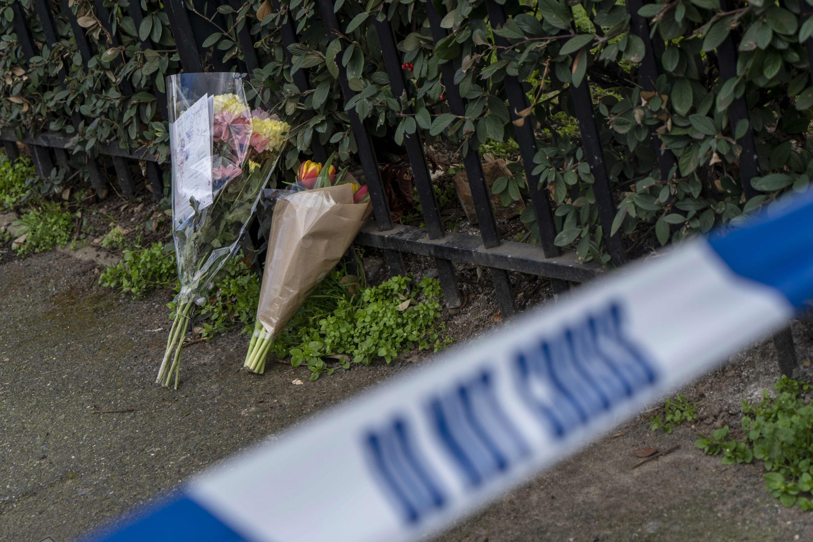 """Bouquets of flowers lie at the scene of the fatal stabbing of a man in Leyton, east London, on March 7, 2019 - The man's death follows a string of high-profile stabbings in recent days which have prompted warnings of a """"national emergency"""" and sparked intense scrutiny of reductions in the size of the police workforce. (Photo by Niklas HALLE'N / AFP)"""