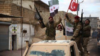 I miliziani dell'Esercito siriano libero, appoggiato dalla Turchia, innalzano la bandiera di Ankara a Manbij il 29 dicembre del 2018 Nazeer Al-Khatib/Afp via LaPresse)