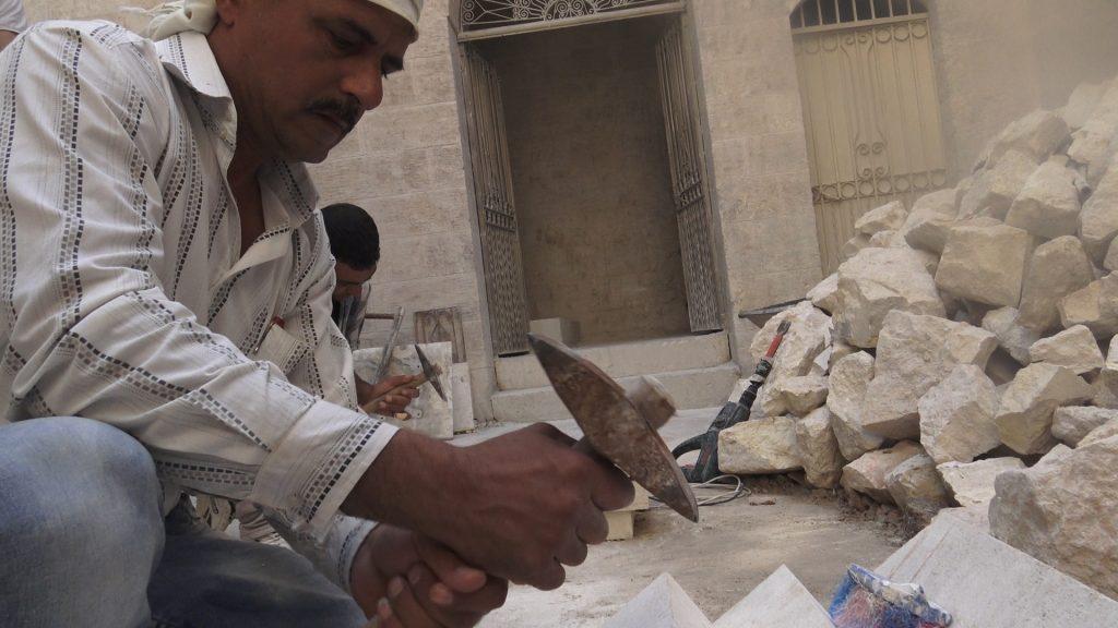 Operai che ricostruiscono la chiesa