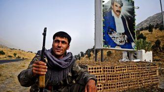 Un combattente curdo davanti a un'immagine di Ocalan (LaPresse)