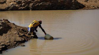 Un uomo raccoglie l'acqua a Laikipia, in Kenya (LaPresse)