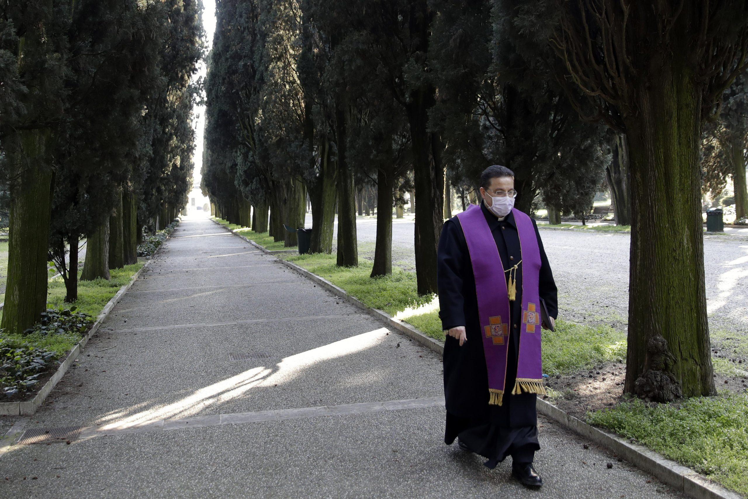 Un sacerdote cammina all'interno del cimitero monumentale di Brescia, detto Vantiniano, dopo aver benedetto le bare di alcune vittime di Covid-19 (LaPresse)