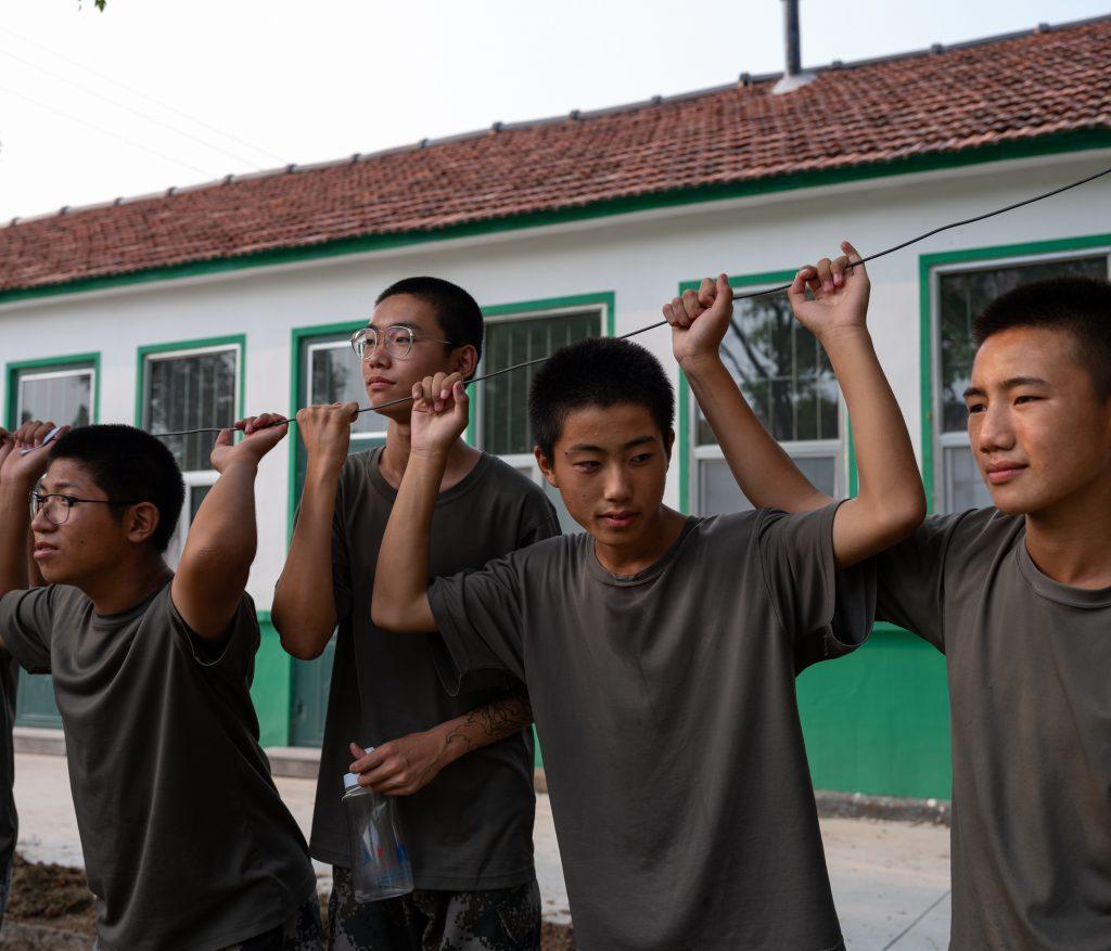 I ragazzi si riposano e aspettano il loro turno per esercitazioni fisiche nel giardino del campo di recupero da dipendenze da internet e videogaming, Weifang