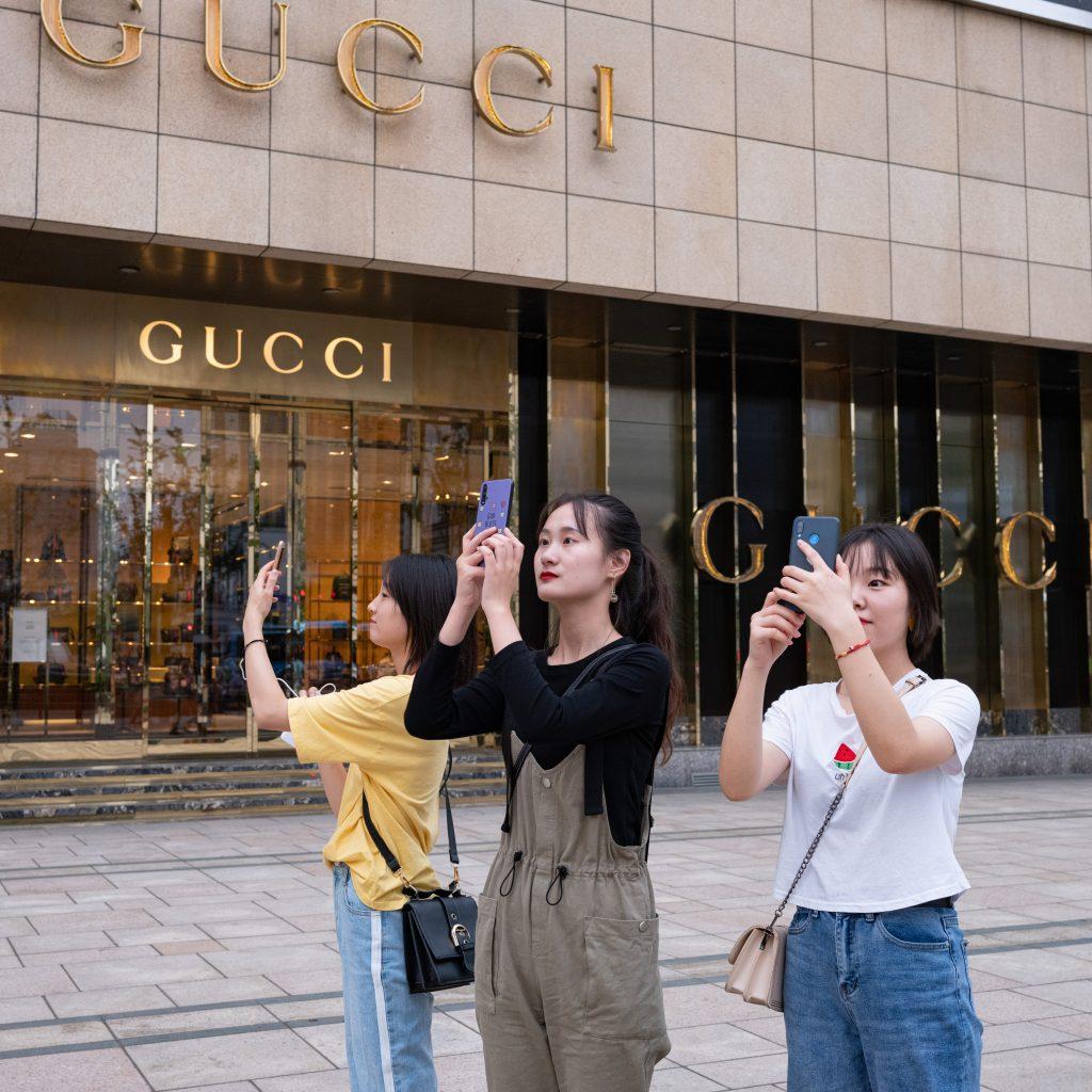 Giovani ragazzi davanti una delle tante vetrine di famosi brand di lusso internazionale nel centro di Wuxi