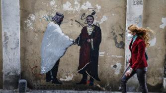 Roma, murale di Harry Greb che ritrae Matteo Renzi che stringe la mano a Mohammed bin Salman (La Presse)