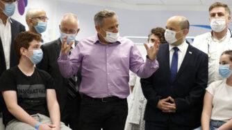 Israeli Prime Minister Naftali Bennett, center right, listens as Health Minister Nitzan Horowitz speaks during his visit to a Maccabi healthcare maintenance organisation in Israel